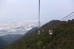 缆车在美丽的绿色山、海湾和城市 免版税库存照片
