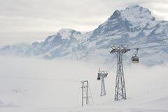缆车长平底船移动滑雪者上升在滑雪胜地在格林德瓦,瑞士 免版税库存图片