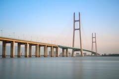 缆绳停留了桥梁在黄昏 免版税库存照片