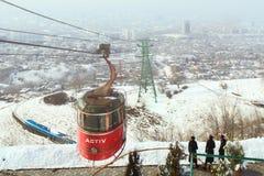 缆索铁路有有雾的市的看法阿尔玛蒂,哈萨克斯坦 图库摄影
