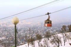 缆索铁路有有雾的市的看法阿尔玛蒂,哈萨克斯坦 免版税库存图片