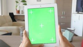 缓慢滑在有绿色屏幕色度大模型的一台数字式片剂个人计算机 股票录像