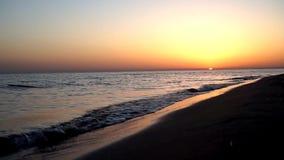 缓慢镇静满意挥动碰撞在沙子海滩在引人入胜的温暖的晚上橙色日落海景的海岸海岸线 股票录像