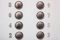 编号在电梯的按钮在灰色背景 免版税库存图片