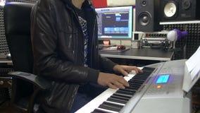 编排者在音乐生产概念的录音室递演奏键盘 股票录像