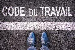 编码du辛苦意思劳方代码用在柏油路背景写的法语与腿 免版税库存照片