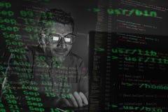 编程和乱砍手提电脑系统的大玻璃的奇怪的整洁和书呆子黑客人键入夜间危险的代码 图库摄影