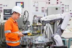 编程机器人产业的工程师在汽车制造业 免版税库存照片