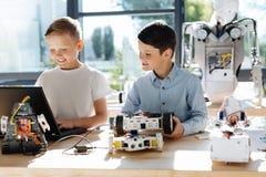 编程他们的机器人汽车的青春期前的男孩 免版税库存图片