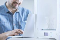 编程3D打印机的人 免版税库存照片