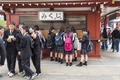 编组买omikuji的o男小学生和女孩纸时运Sensoji东京 免版税图库摄影