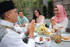 编组拥抱每其他在餐桌里的愉快的年轻穆斯林 免版税库存图片