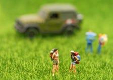 编组站立在游人和冒险的森林里的微型旅客和远足者背包 库存照片