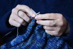 编织一件羊毛毛线衣,在针的焦点的妇女 免版税库存照片