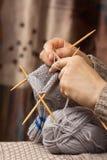 编织与竹针的手一只袜子 免版税库存照片