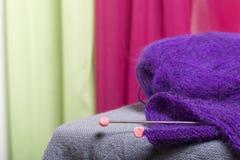 编织与钢编织针 紫色螺纹和钢编织针球在未完成的编织 免版税库存照片