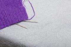 编织与钢编织针 紫色螺纹和钢编织针球在未完成的编织 免版税库存图片