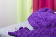 编织与钢编织针 紫色螺纹和钢编织针球在未完成的编织 库存照片