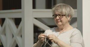 编织和微笑户外对老人院射击的年长妇女的愉快的退休坐红色照相机 影视素材