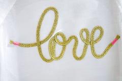 编织在白色纺织品的金手工艺文本爱错别字 免版税库存照片