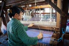 编织在织布机的地方Intha妇女绿色莲花织品在地方莲花布料编织的车间在Inle湖,掸邦,缅甸 免版税库存图片