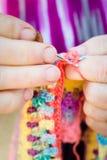 编织在编织针的一个老妇人的手特写镜头,使用五颜六色的羊毛 免版税图库摄影