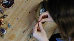 编织小珠 妇女` s的特写镜头在车间递串起在螺纹的小珠,做首饰 回到视图 股票录像