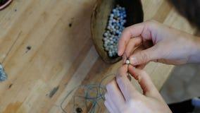 编织小珠 妇女` s的特写镜头在车间递串起在螺纹的小珠,做首饰 股票录像