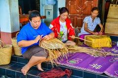 编织柳条提包的妇女做由纸莎草 库存图片