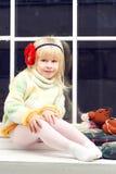 编织毛线衣和查找的小女孩照相机 免版税图库摄影