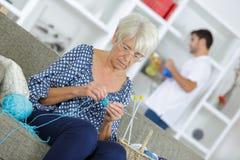 编织由窗口的老妇人 免版税库存图片