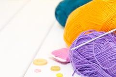 编织的棉花螺纹、勾子和按钮在桌上 库存图片