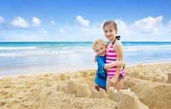 编译在海滩的子项沙堡 免版税库存图片