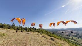 编辑与橙色滑翔伞的滑翔伞起飞 免版税库存图片