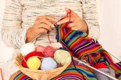 编织一条五颜六色的围巾的妇女 免版税库存图片