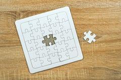 编结从七巧板的失踪在木桌上 免版税库存图片