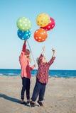 编组两个滑稽的白色白种人儿童孩子画象与五颜六色的束的气球,演奏跑在日落的海滩 库存图片
