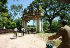 编组亚洲孩子,乘坐的自行车,高棉村庄门 库存图片