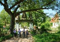 编组亚洲孩子,乘坐的自行车,高棉村庄门 免版税图库摄影