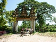 编组亚洲孩子,乘坐的自行车,高棉村庄门 免版税库存图片