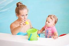 编组使用与玩具的白白种人母亲和小女儿画象在引导游泳的poo的水中里面,训练对s 免版税库存照片