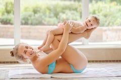 编组做体育健身锻炼瑜伽的白白种人母亲和小女儿画象一起说谎在swimmi的地板上 免版税图库摄影