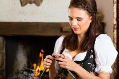 编织在猎人的客舱或高山小屋的妇女 图库摄影