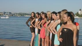 编组在站立在行的礼服的模型在海附近 影视素材