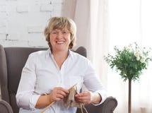 编织在轮幅的一名微笑的中年妇女的画象 免版税库存照片