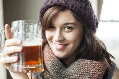 被编织的围巾和帽子饮料啤酒的美丽的少妇 免版税库存照片