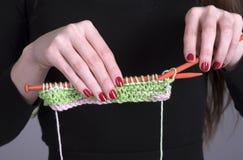 编织围巾的手与羊毛一起使用和针 库存照片