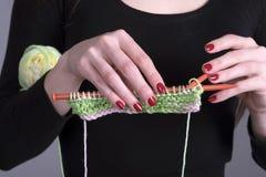 编织围巾的手与羊毛一起使用和针 免版税库存图片