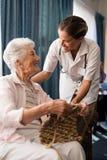 编织微笑的资深的妇女,当看女性医生时 库存图片