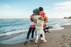 编组白色白种人家庭,有拥抱微笑的笑在海洋在日落的海海滩的三个儿童孩子的母亲画象  图库摄影